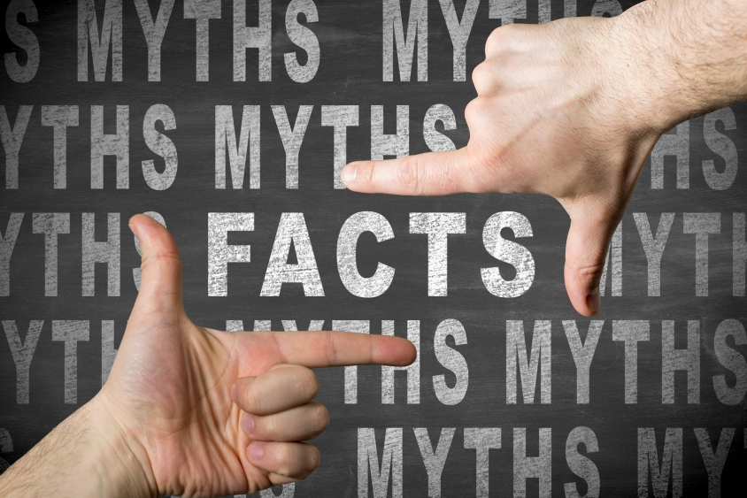 "Man finger framing the word ""facts"" among many words ""myths"" written with chalk on a blackboard"