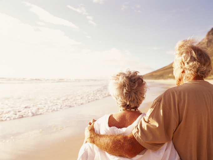 Photo of senior couple embracing each other while walking on the beach